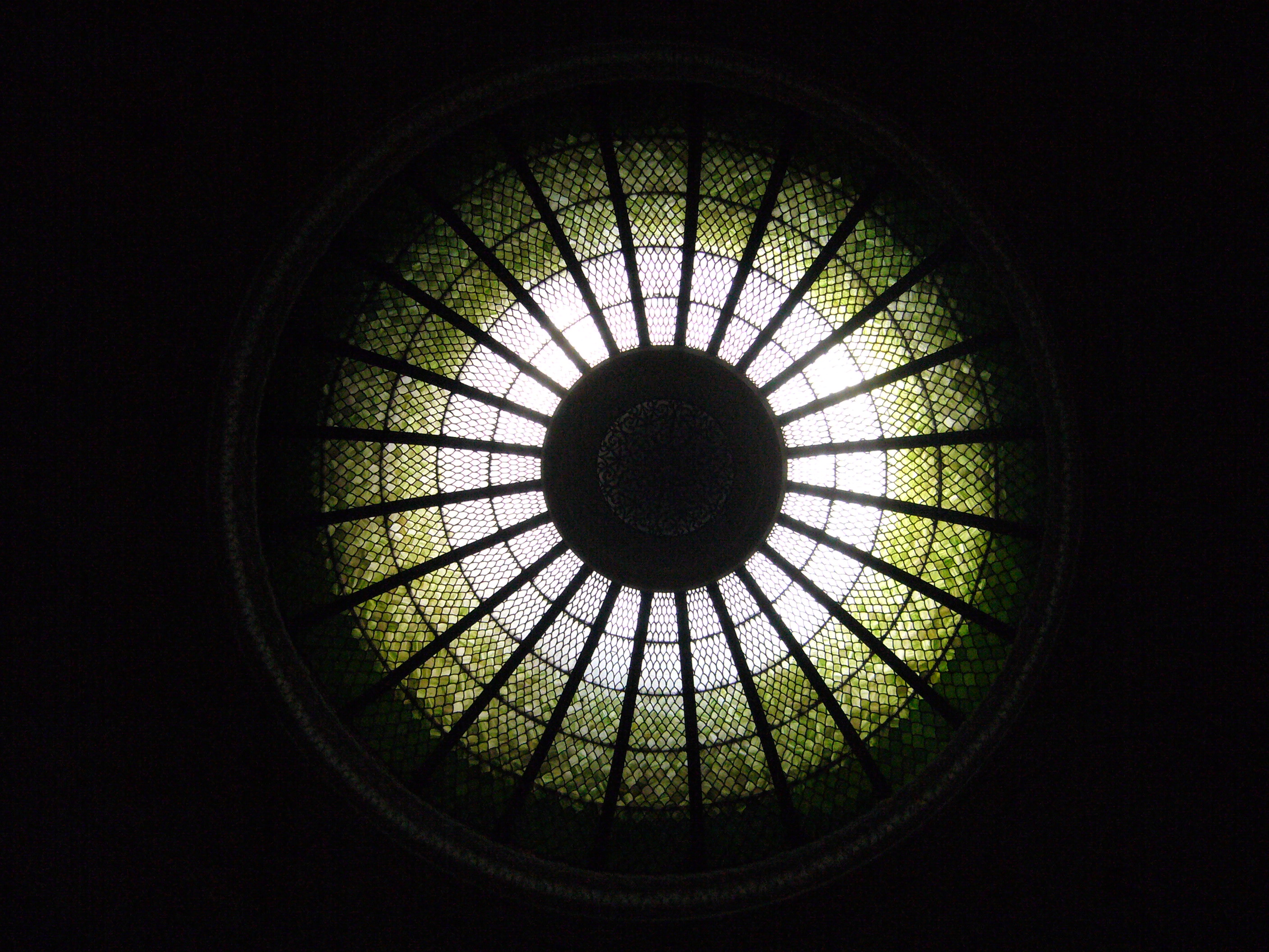 A view of a stained glass dome from the ground below it.