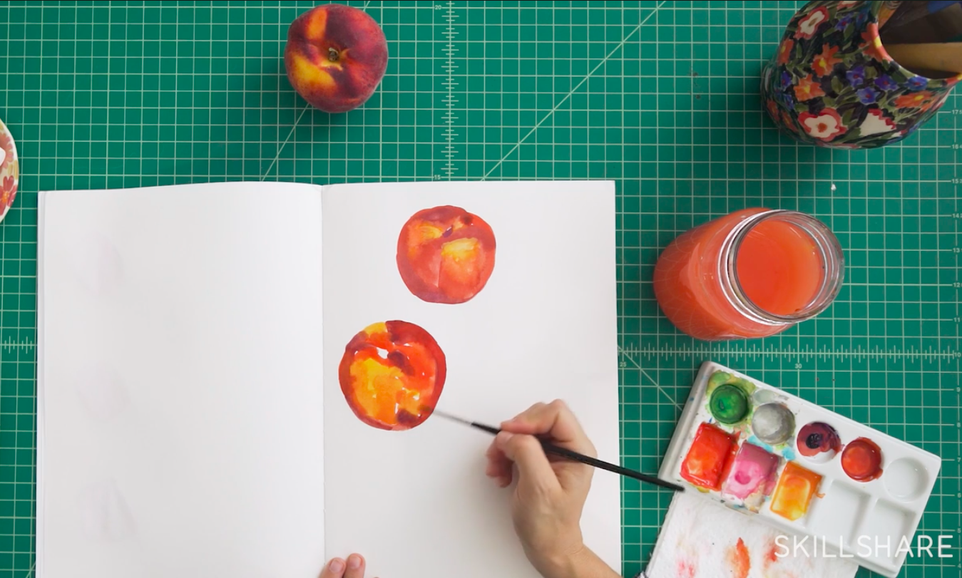 A view from above of an open sketchbook with two loosely painted peaches. Next to the book is a paint palette and a jar of paint water.